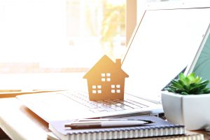 Wood house model on computer laptop